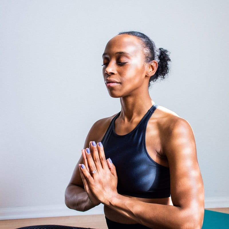 woman meditating with hands in prayer position