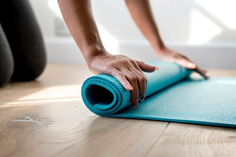 person rolling out blue non slip yoga mat